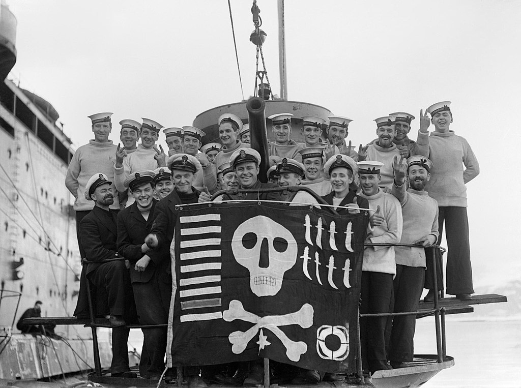 The crew of HM Submarine Utmost displaying their Jolly Roger
